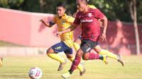 Bek kiri Persis Solo, Gufroni Al Ma'ruf (seragam merah) saat ditempel pemain Persika Karanganyar dalam uji coba di Stadion UNS, Surakarta, Rabu (7/10/2020). (Bola.com/Vincentius Atmaja)