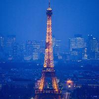 """Lansekap kota Paris dari atap gedung pencakar langit """"The Tour Montparnasse"""" memperlihatkan Menara Eiffel, Senin (8/1). Wisatawan dibuat tak percaya saat memandangi luasnya panorama kota saat malam yang bermandikan cahaya lampu. (CHRISTOPHE SIMON/AFP)"""