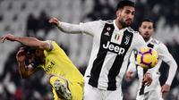 Pemain Chievo, Sergio Pellissier berebut bola dengan gelandang Juventus, Emre Can pada laga pekan ke-20 Serie A di Allianz Stadium, Senin (21/1). Juventus berhasil memantapkan posisi di puncak klasemen setelah menggilas Chievo 3-0. (Marco BERTORELLO/AFP)