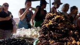 Wisatawan mengambil gambar tarantula goreng yang dijajakan sebuah kios di wilayah Skun, Provinsi Kampong Cham, Kamboja, 14 Maret 2018. Penduduk setempat menyebut, tarantula goreng rasanya seperti daging kepiting. (TANG CHHIN Sothy / AFP)