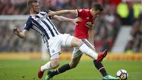 Aksi pemain West Bromwich, Chris Brunt (kiri) menutup ruang gerak pemain Manchester United, Ander Herrera pada lanjutan Premier League di Old Trafford, Manchester,(15/4/2018). Manchester United kalah 0-1. (Nick Potts/PA via AP)