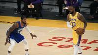Pemain LA Lakers, LeBron James, mengontrol bola dengan dikawal pemain LA Clippers, Paul George, pada laga pembuka NBA 2020/2021, di Staples Center, Rabu (23/12/2020) pagi WIB. (AFP/Harry Haw)