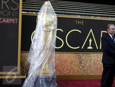 Seorang penjaga keamanan berdiri di samping patung Oscar yang ditutupi plastik pada pintu masuk ke teater Dolby saat persiapan ke-88 Academy Awards di Hollywood, Los Angeles , California, (27/2). (REUTERS / Lucy Nicholson)
