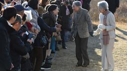 Kaisar Jepang Akihito dan Permaisuri Michiko menyapa warga saat berjalan-jalan di pantai dekat villa miliknya, Prefektur Kanagawa, Senin (21/1). Akihito akan turun takhta pada 30 April 2019, mengakhiri pemerintahan selama tiga dekade. (Kazuhiro NOGI/AFP)