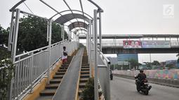 Pejalan kaki melintasi jembatan penyeberangan orang (JPO) di Jalan Yos Sudarso, Jakarta, Kamis (8/11). Kondisi JPO yang rusak menggangu kenyamanan dan keselamatan pejalan kaki. (Merdeka.com/Iqbal Nugroho)