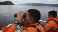 Tim SAR menggunakan teropong saat proses pencarian korban KM Sinar Bangun yang tenggelam di Danau Toba, Sumatra Utara, Rabu (20/6). Hingga hari ketiga, sebanyak 18 penumpang selamat, dua tewas dan 160 lainnya dalam proses pencarian. (AP/Binsar Bakkara)