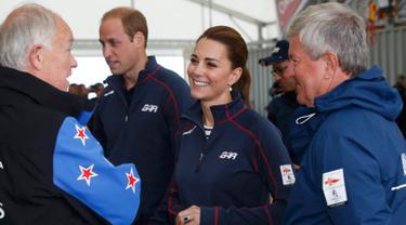 Kate Middleton bersama Pangeran William berbincang dengan para pejabat saat menghadiri America's Cup World Series setiba di markas Emirates Tim Selandia Baru di Royal Naval Dockyard, Inggris (26/7/2015). (REUTERS/Luke MacGregor)