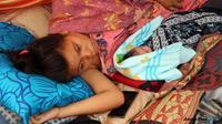 Elmiyanti bersama anak laki-lakinya yang baru lahir saat gempa susulan masih terjadi di Lombok, Nusa Tenggara Barat. (Foto: Pujo/Lombok Post/Jawa Pos Group)