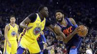 Forward Golden State Warriors Draymond Green (kiri) menjaga bintang Oklahoma City Thunder Paul George pada partai NBA di Oracle Arena, Sabtu (24/2/2018) atau Minggu (25/2/2018) WIB. (AP Photo/Marcio Jose Sanchez)