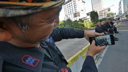 Sejumlah Korps Brimob berfoto disela penjagaan mereka di kawasan MH Thamrin, Jakarta, Jumat (24/5/2019). Usai kerusuhan 22 Mei 2019, penjagaan di kawasan jalan MH Thamrin sampai Jumat, 24 Mei 2019 masih terus dilakukan oleh aparat kepolisian. (Liputan6.com/Herman Zakharia)