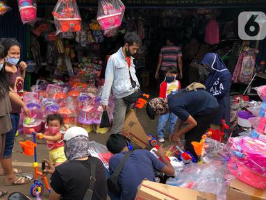 Warga memilih mainan tanpa menjaga jarak di Pasar Gembrong, Jakarta Timur, Minggu (31/5/2020). Meski penerapan masa Pembatasan Sosial Berskala Besar (PSBB) di Jakarta masih berlaku, namun pasar yang khusus menjual pernak-pernik mainan anak ini kembali dipadati warga. (Liputan6.com/Immanuel Antonius)