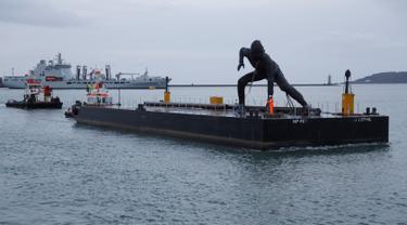 Patung perunggu terbesar di Inggris,  berjudul 'Messenger' tiba dengan tongkang di pesisir pantai Plymouth, Senin (18/3). Patung perunggu tersebut diciptakan oleh seorang pematung berusia 44 tahun bernama Joseph Hillier. (REUTERS/Peter Nicholls)