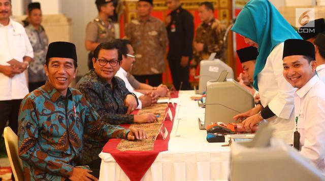 Presiden Joko Widodo (kiri) dan Sekretaris Kabinet Pramono Anung ketika menyerahkan zakat mal di Istana Negara, Jakarta, Kamis (16/5/2019). Jokowi bersama para menteri, kepala lembaga, hingga direksi BUMN melakukan pembayaran zakat mal melalui Baznas. (Liputan6.com/Angga Yuniar)
