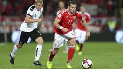 Pemain Wales, Gareth Bale melewati adangan pemain Austria pada laga Group D kualifikasi Piala Dunia 2018 di Cardiff City Stadium, Cardiff, (2/8/2017). Wales menang 1-0. (David Davies/PA via AP)
