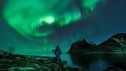 Seorang surfer membawa papannya melihat Cahaya Utara atau aurora borealis di Utakleiv, Norwegia utara (9/3). Biasanya aurora terjadi di daerah di sekitar kutub Utara dan kutub Selatan magnetiknya. (AFP/Olivier Morin)