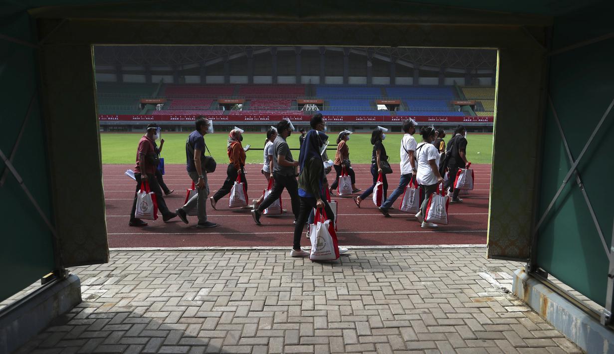 Warga berjalan kaki untuk menerima vaksin Sinovac saat vaksinasi massal virus corona COVID-19 untuk umum di Stadion Patriot Candrabhaga, Bekasi, Jawa Barat, Senin (14/6/2021). Peminat vaksinasi COVID-19 di Stadion Patriot Candrabagha sangat tinggi. (AP Photo/Achmad Ibrahim)