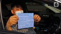 Pengendara menunjukkan surat tilang di kawasan Fatmawati, Jakarta, Senin (10/8/2020). Ditlantas Polda Metro Jaya kembali menerapkan sanksi tilang terhadap kendaraan roda empat yang melanggar peraturan ganjil genap di masa Pembatasan Sosial Berskala Besar transisi. (Liputan6.com/Herman Zakharia)