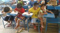 Tidak ingin ketinggalan mata pelajaran dan mengutamakan pendidikan, bocah ini mengasuh adiknya di sekolah.