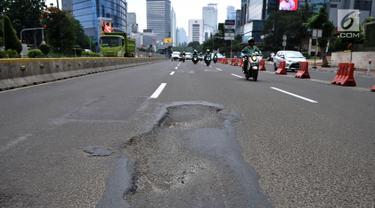 Kondisi jalanan yang berlubang di Jalan Jenderal Sudirman, Jakarta, Senin (11/3). Minimnya perawatan dan pengawasan membuat jalan tersebut berlubang hingga kedalaman 10 sentimeter. (merdeka.com/Iqbal S. Nugroho)