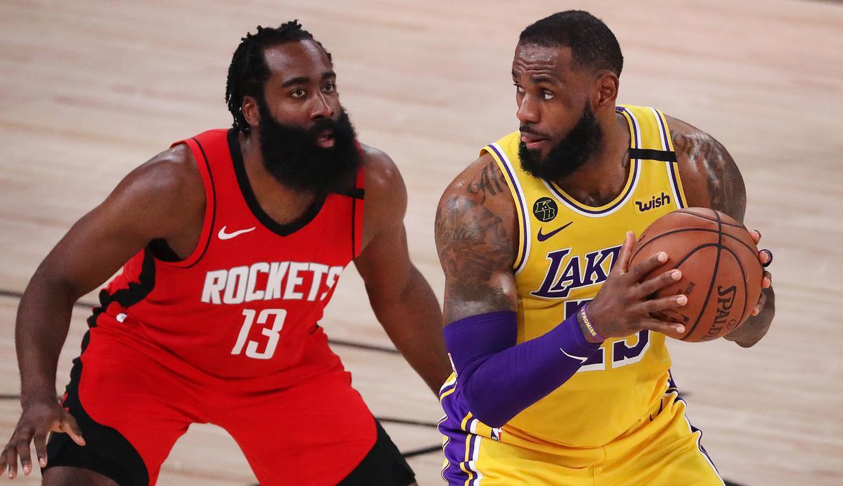 Pebasket LA Lakers, LeBron James, berebut bola dengan pebasket Houston Rockets, James Harden, pada semifinal playoff NBA di ESPN Wide World Sports, Orlando, Jumat (11/9/2020). LA Lakers menang 110-100 atas Houston Rockets. (AFP/Michael Reaves/Getty Images)