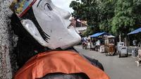 Para perajin menyelesaikan pembuatan ondel-ondel di Kramat Pulo, Senen, Jakarta, Rabu (10/2/2021). Pendapatan sejumlah sanggar ondel-ondel di Kramat Pulo merosot karena larangan menggelar pesta pernikahan atau sejenisnya selama pandemi. (merdeka.com/Iqbal S. Nugroho)