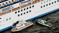 Kapal patroli Japan Coast Guard mengevakuasi penumpang dan kru kapal pesiar Diamond Princess ke rumah sakit di lepas pantai Yokohama, Jepang,  Rabu (5/2/2020). Sebanyak 10 orang di kapal pesiar tersebut dinyatakan positif terinfeksi virus corona. (Hiroko Harima/Kyodo News via AP)