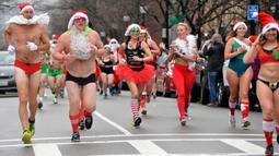 Pelari berjalan menyusuri Newbury Street selama Santa Speedo Run di Boston, Massachusetts, Sabtu (14/12/2019). Speedo Run adalah perlombaan lari menjelang Natal dengan peserta pria hanya menggenakan celana dalam dan wanita memakai bikini beserta topi ala Sinterklas. (Joseph Prezioso/AFP)