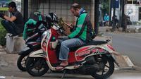 Driver ojek online beristirahat di kawasan Jakarta, Jumat (10/4/2020). Peraturan Gubernur DKI Jakarta dalam pelaksanaan PSBB mengatur angkutan roda dua seperti ojek online maupun ojek konvensional dilarang membawa penumpang.  (Liputan6.com/Herman Zakharia)