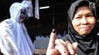 Warga menunjukkan jarinya yang telah dicelup tinta seusai menggunakan hak pilihnya pada Pemilu 2019 di TPS 073, Gunung Balong 1, Lebak Bulus, Jakarta Selatan, Rabu (17/4). TPS 073 ini mengambil tema horor, di mana para petugasnya mengenakan kostum beragam jenis hantu. (merdeka.com/Arie Basuki)
