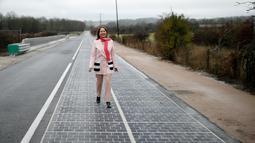 Menteri Ekologi, Pembangunan Berkelanjutan, dan Energi Prancis, Segolene Royal berdiri di jalan raya dengan panel surya saat peresmian di Tourouvre, Normandia (22/12). (Reuters/Benoit Tessier)