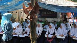 Guru mengajar siswa kelas 8 SMP  1 Cijeruk Terbuka di tempat belajar beratapkan terpal di halaman rumah warga di Kampung Cijeruk RT 002/005, Desa Palasari, Kecamatan Cijeruk, Kabupaten Bogor, Jawa Barat, Senin (2/9/2019). (merdeka.com/Arie Basuki)