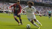 """Pemain Real Madrid, Marcelo (kanan) mengecoh pemain Levante, David Remeseiro """"Jason"""" pada lanjutan La Liga di Santiago Bernabeu stadium, Madrid (9/9/2017). Madrid bermain imbang 1-1. (AP/Francisco Seco)"""
