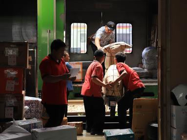 Pekerja mengangkat sepeda motor ke dalam truk yang akan dikirim di Stasiun Pasar Senen, Jakarta, Selasa (5/6). Jasa pengiriman motor ke daerah meningkat dua kali lipat jelang arus mudik dan Hari Raya Idulfitri 2018. (Liputan6.com/Arya Manggala)