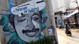Pengendara melintas di sisi mural bergambar aktivis HAM, Munir di Jalan Ciledug Raya, Jakarta, Senin (7/9/2020). 7 September, 16 tahun lalu, pejuang kemanusiaan Munir Said Thalib meninggal dunia setelah diracun dalam penerbangan menuju Amsterdam, Belanda. (Liputan6.com/Helmi Fithriansyah)