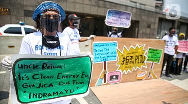 Sejumlah warga dari Indramayu membawa poster saat menggelar aksi di depan Kedubes Jepang, Jakarta, Rabu (21/10/2020). Dalam aksinya, mereka menolak pembangunan PLTU 2 di Indramayu karena akan menyebabkan pencemaran udara dan rusaknya lahan pertanian. (Liputan6.com/Faizal Fanani)