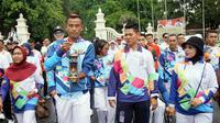 Salah seorang atlet para atletik sedang membawa lentera didampingi Ketua Inapgoc, Raja Sapta Oktahari.(Liputan6.com/Fajar Abrori)