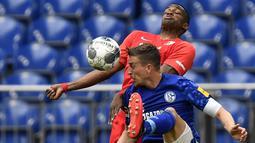 Pemain Augsburg, Felix Uduokha berebut bola dengan Schalke 04, Bastian Oczipka, pada laga Bundesliga di Veltins-Arena, Minggu (24/5/2020). Augsburg menang dengan skor 3-0 atas Schalke 04. (AP/Martin Meissner)