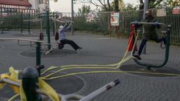 Dua wanita lansia berolahraga di sebuah taman di Beograd, Serbia (21/4/2020). Para lansia diberi kesempatan keluar rumah selama 30 menit pada Selasa, Jumat, dan Minggu. (AFP/Oliver Bunic)