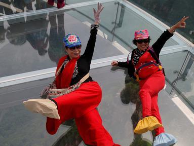 Dua turis berselfie saat mengunjungi wahana platform kaca di Shilin Gorge, Beijing, Cina, (27/5). Platform kaca ini merupakan yang terpanjang di dunia mengalahkan Grand Canyon. (REUTERS/Kim Kyung-Hoon)