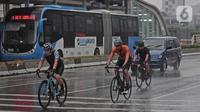 Warga bersepeda saat hujan turun di kawasan Bundaran HI, Jakarta, Minggu (24/1/2021). Kepala BMKG Dwikorita mengatakan, puncak musim hujan akan terjadi pada Januari dan Februari 2021, sehingga perlu diwaspadai terjadinya cuaca ekstrem. (Liputan6.com/Herman Zakharia)