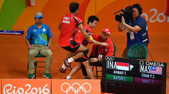 Tontowi Ahmad dan Liliyana Natsir merayakan kemenangan bersama pelatihnya Richard Mainaky usai meraih medali emas Olimpiade Rio 2016 saat mengalahkan Peng Soon Chan dan Liu Ying Goh dari Malaysia. (AFP/Ben Stansall)