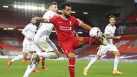 Penyerang Liverpool, Mohamed Salah, berebut bola dengan pemain Leeds United, Stuart Dallas, pada laga Premier League di Stadion Anfield, Minggu (13/9/2020). Liverpool menang dengan skor 4-3. (Shaun Botterill, Pool via AP)