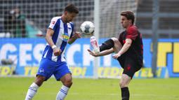 Pemain Hertha Berlin, Marko Grujic, berebut bola dengan pemain Augsburg, Raphael Framberger, pada laga Bundesliga di Olympiastadion, Sabtu (30/5/2020). Hertha Berlin menang 2-0 atas Augsburg. (AP/Hannibal Hanschke)