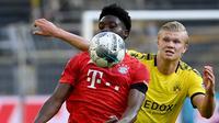 Gelandang Bayern Munchen, Alphonso Davies, berebut bola dengan striker Borussia Dortmund, Erling Braut Haaland, pada laga pekan ke-28 Bundesliga di Stadion Signal Iduna Park, Selasa (26/5/2020) waktu setempat. Bayern Munchen menang 1-0 atas Borussia Dortmund. (AFP/Federico Gambarini/Pool)