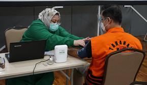 Mantan Menteri Sosial (Mensos) Juliari Peter Batubara dan para tahanan kasus korupsi KPK lainnya melakukan vaksinasi Covid-19 tahap pertama. (Humas KPK)