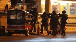 Sejumlah tentara komando bersenjata terlihat di luar mal Terminal 21 Korat saat terjadi penembakan di Nakhon Ratchasima, Thailand, Minggu (9/2/2020). Petugas langsung mengevakuasi pengunjung dari dalam mal Terminal 21 Korat. (AP Photo/Sakchai Lalitkanjanakul)