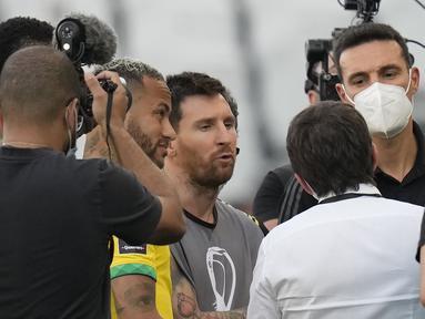 Penyerang Argentina, Lionel Messi, pemain Brasil Neymar dan pelatih Lionel Scaloni berbicara saat pertandingan dihentikan otoritas kesehatan selama pertandingan kualifikasi Piala Dunia FIFA Qatar 2022 di stadion Neo Quimica Arena di Sao Paulo, Brasil, Minggu (5/9/2021).  (AP Photo/Andre Penner)