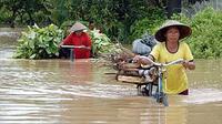Dua pencari kayu dan pakan ternak melintasi banjir di Desa Wonoasri, Tempurejo, Jember, Jawa Timur.(Antara)