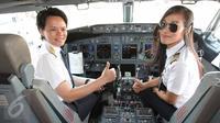 Kapten pilot Garuda Indonesia Ida Fiqria (kiri) dan kopilot Sari Ardisa bersiap menerbangkan pesawat di bandara Minangkabau, Padang, Sumbar, Jumat (21/4). Peringati hari Kartini 2017, pesawat seluruhnya diawaki oleh perempuan. (Liputan6.com/Angga Yunair)