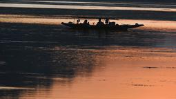 Nelayan menunggu di perahu kecil setelah memancing di Danau Dal saat matahari terbenam di Srinagar (9/9/2019). Di Sepanjang tepi Danau Dal terdapat Ghate yang merupakan tempat bersandarnya Shikara. (AFP Photo/Tauseef Mustafa)